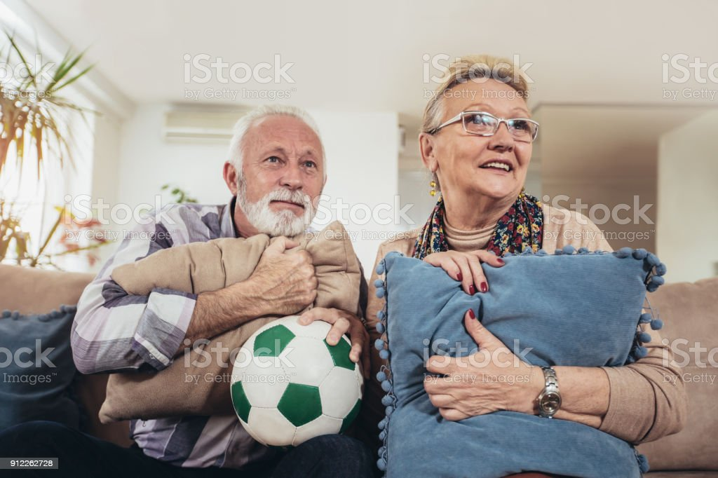 Happy senior couple watching soccer on tv and celebrating victory at...