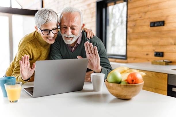 Happy senior couple waving to someone over video call at home. stock photo