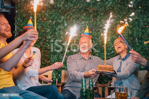 Family and friends at outdoor birthday party with a cake and mini fireworks in their hands