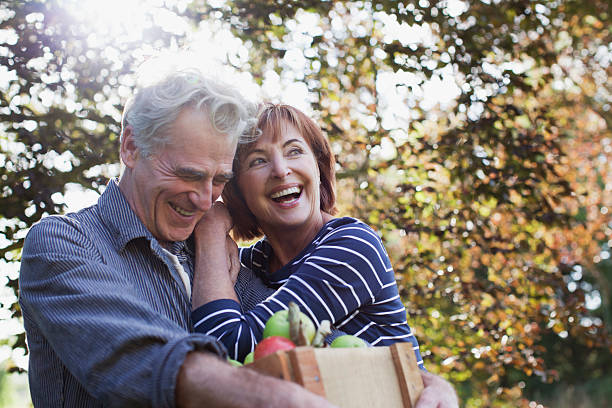 Happy senior couple with bushel of apples hugging  65 69 years stock pictures, royalty-free photos & images