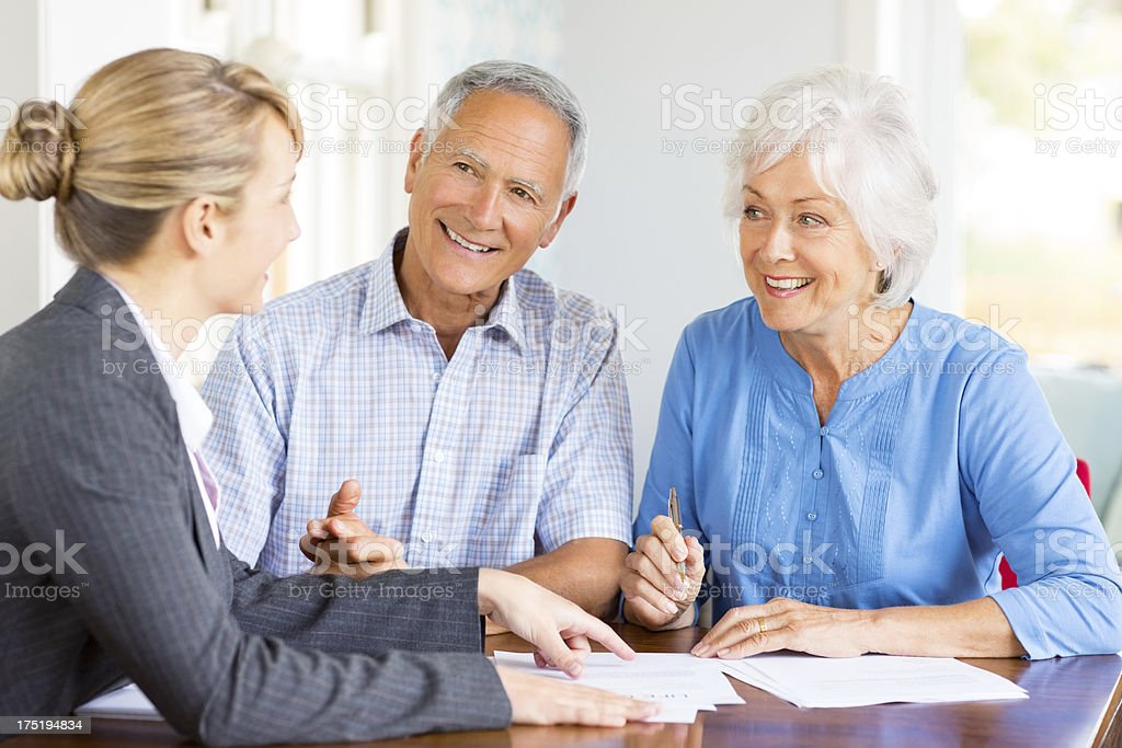 Happy Senior Couple With Financial Adviser At Home royalty-free stock photo