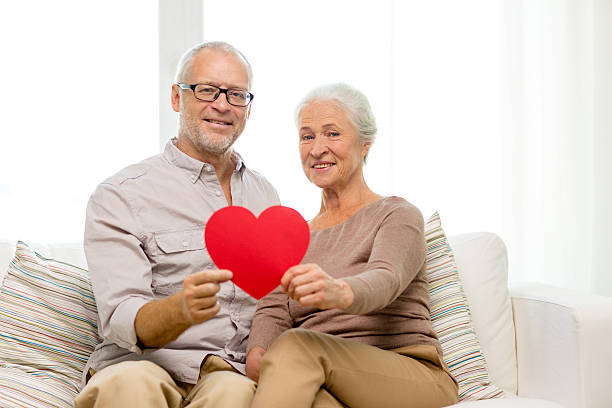 happy senior couple with red heart shape at home - senior valentine stock photos and pictures