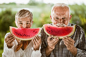 Happy mature couple holding slices of fresh watermelon and looking at camera.
