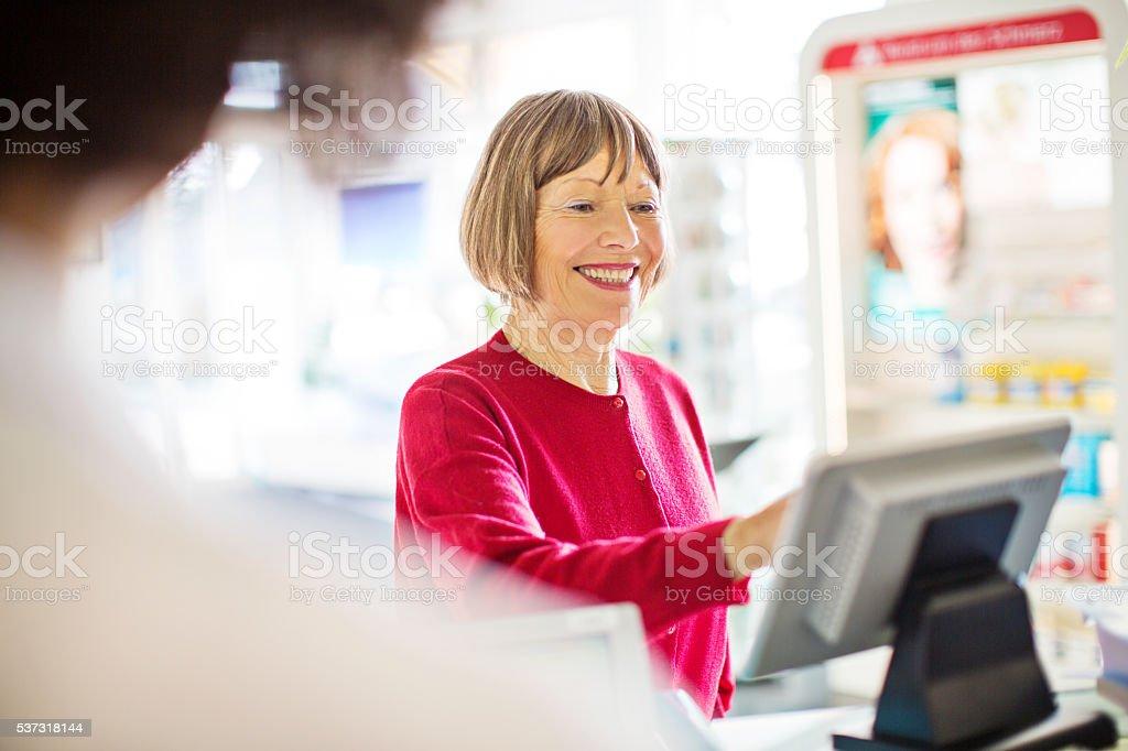 Happy senior customer at pharmacy checkout counter stock photo