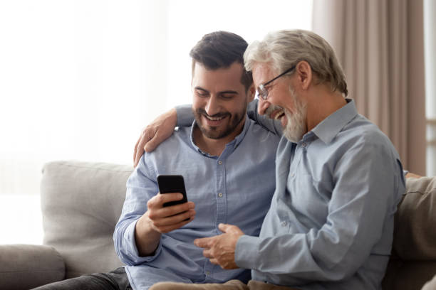 Happy senior dad and millennial son using smartphone together stock photo