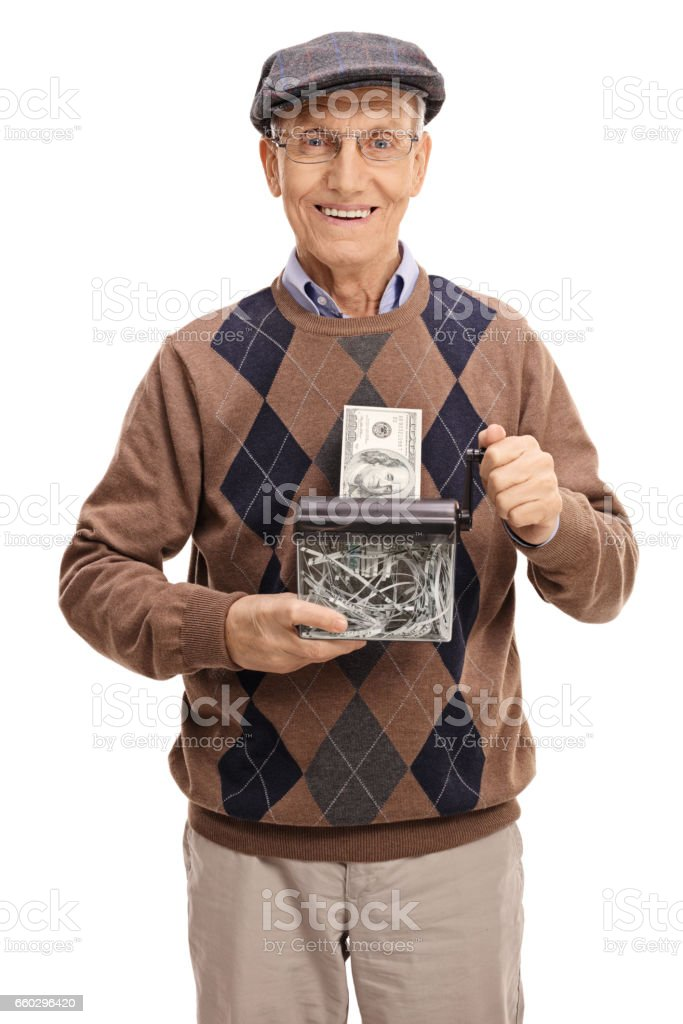 Happy senior destroying a dollar bill in a paper shredder stock photo