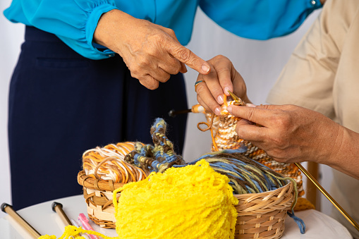 Happy senior elder woman teaching knitting woven craft other old female mature togehter at home as hobby. happiness retirement people