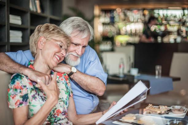Glücklich Senior umarmen paar Lesen einer Zeitschrift in Kaffee-Bar, Slowenien, Europa – Foto