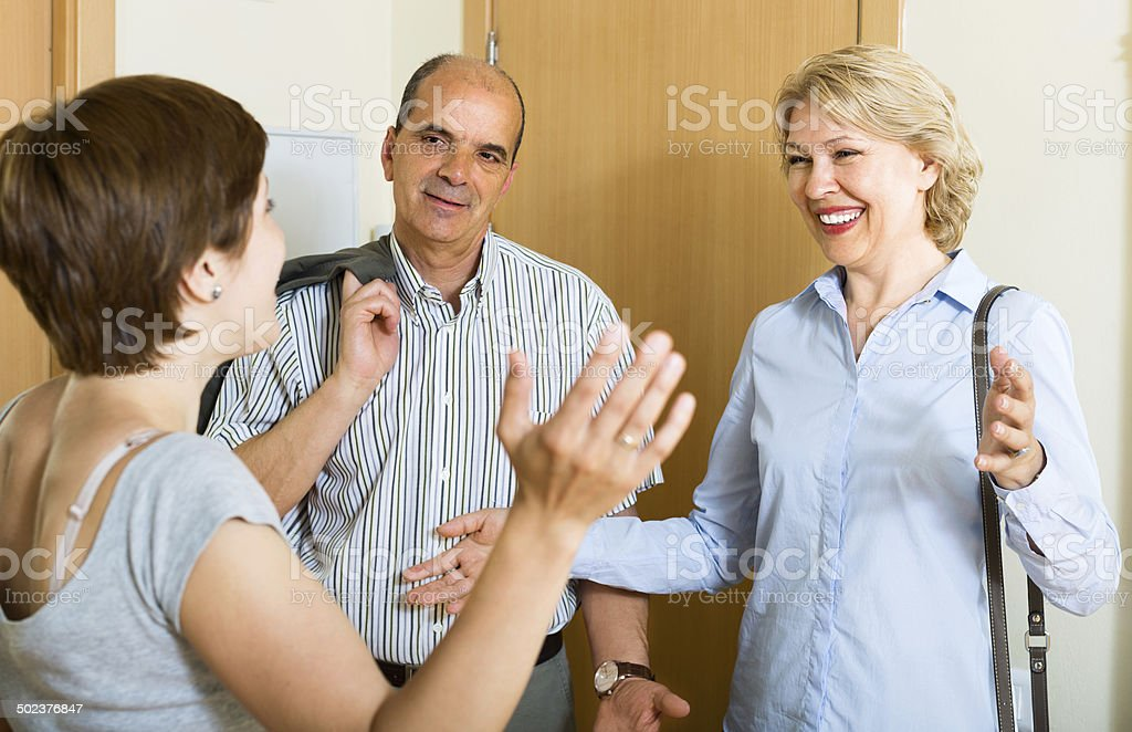 Happy senior family couple visiting adult daughter stock photo
