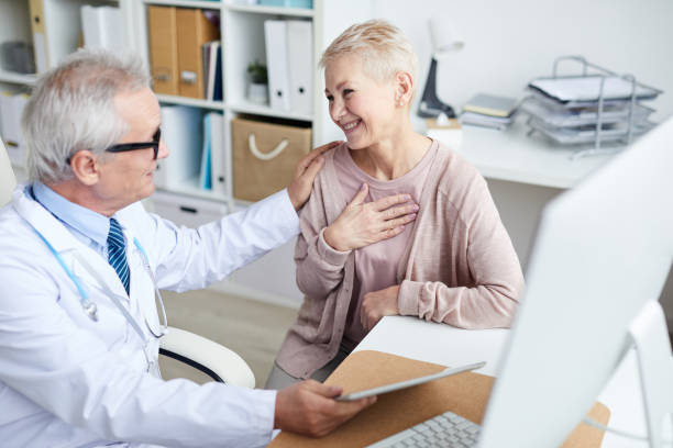 Happy senior female patient with short hair sitting at table in doctors office and holding hand on chest while thanking doctor for good treatment and support stock photo