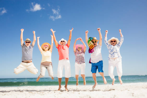Happy senior friends jumping Happy senior friends jumping on the beach young at heart stock pictures, royalty-free photos & images