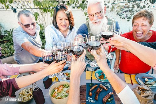 Happy senior friends toasting with red wine glasses at dinner time outdoor - Mature people having fun dining together outside - Elderly lifestyle, food and drink, retired and pensioners concept