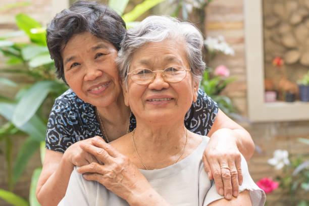 快樂的高級友好社會理念。亞洲老年女性在家中、養老院或福利縣的花園裡快樂地微笑的肖像 - 亞洲 個照片及圖片檔