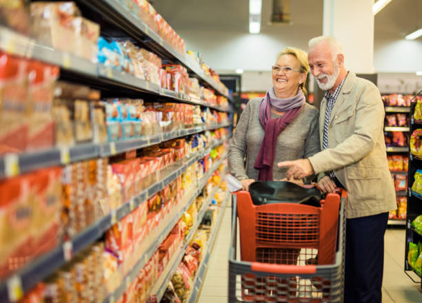 Happy senior grocery grocery shopping. Happy senior grocery grocery shopping. snack aisle stock pictures, royalty-free photos & images