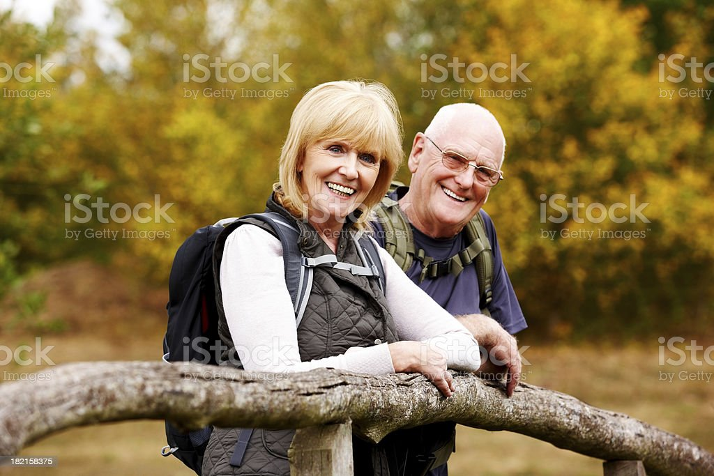 Happy senior hikers standing by a fence royalty-free stock photo
