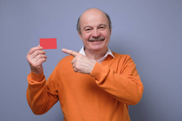 Happy senior hispanic bald man advertising bonus card smiling at camera. stock photo