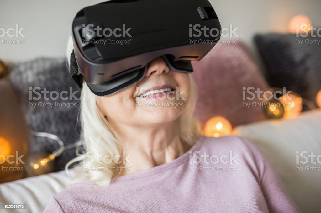 Happy senior lady in vr goggles at home stock photo
