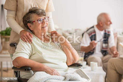 istock Happy senior lady sitting at wheelchair in nursing home for elderly 1080278248