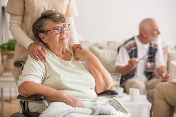 happy senior lady sitting at wheelchair in nursing home for elderly - alzheimer imagens e fotografias de stock