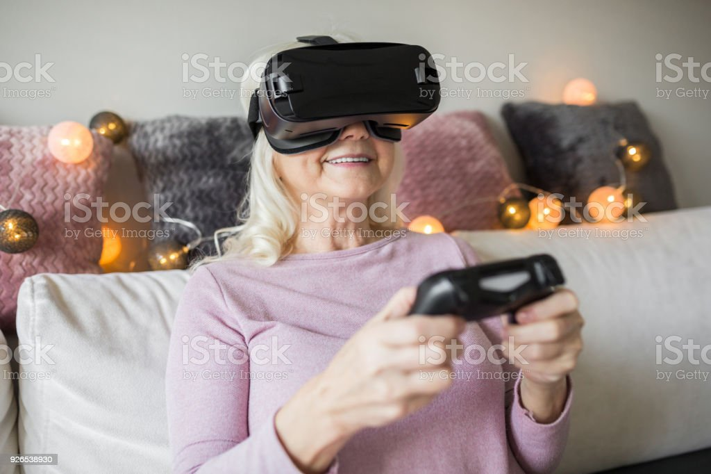 Happy senior lady using vr headset at home stock photo