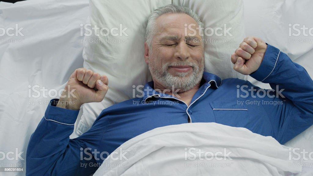 Homem mais velho feliz acordar de bom humor em casa após a bela noite calma - foto de acervo