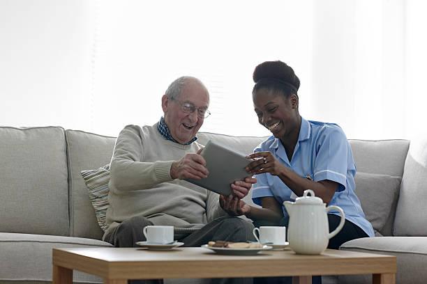 Happy senior man and nurse using digital tablet at home stock photo