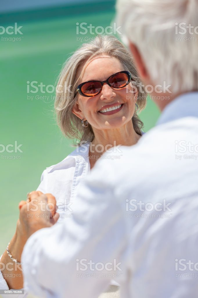04bf031297ef Happy senior man and woman couple dancing and holding hands on a deserted  tropical beach with