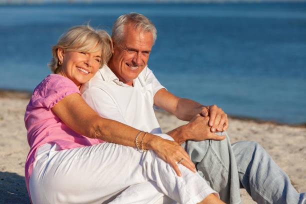 Feliz pareja de ancianos hombre y mujer sentado sonriente y riendo en una playa tropical desierta con mar azul - foto de stock