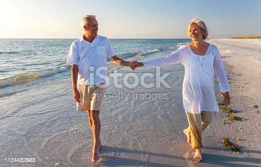 istock Happy senior man and woman couple walking and holding hands on a deserted tropical beach with bright clear blue sky 1124432663