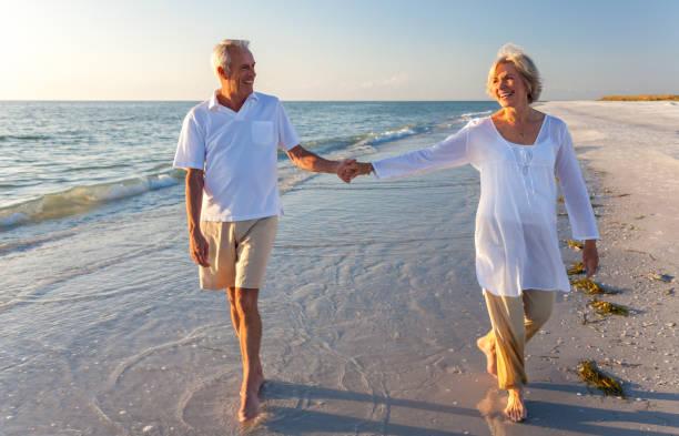 Senior hombre y mujer pareja feliz caminando y cogidos de la mano en una playa tropical desierta con cielo azul brillante - foto de stock