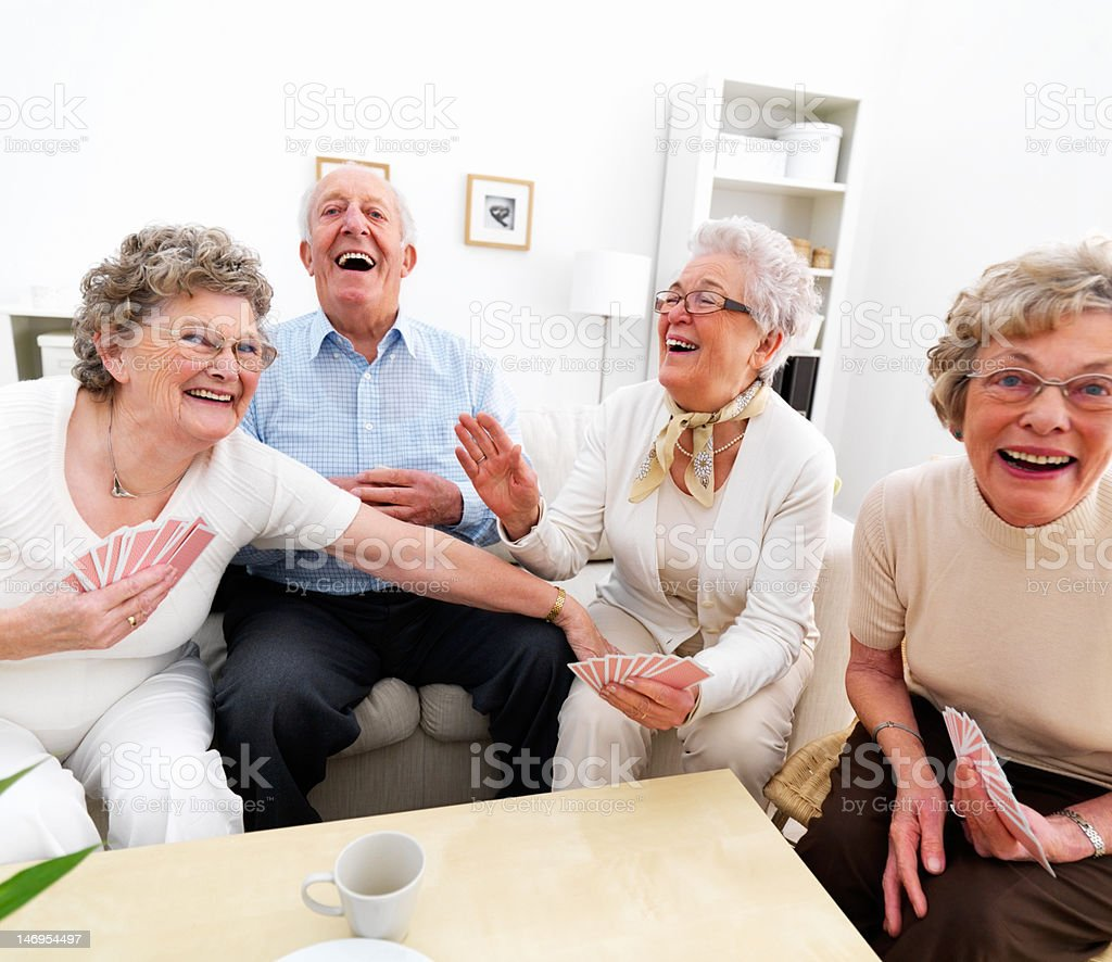 Happy senior man and women playing cards at home stock photo