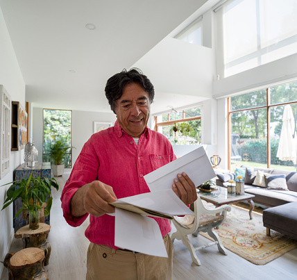 Happy senior man at home going over his mail smiling