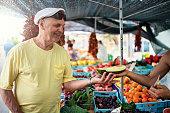 Happy senior man buying melon at Spanish farmer's market.\nNikon D850