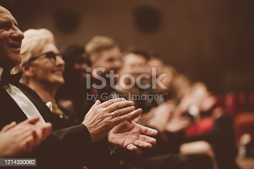 585298714 istock photo Happy senior man clapping in the theater, focus on hands 1214330062