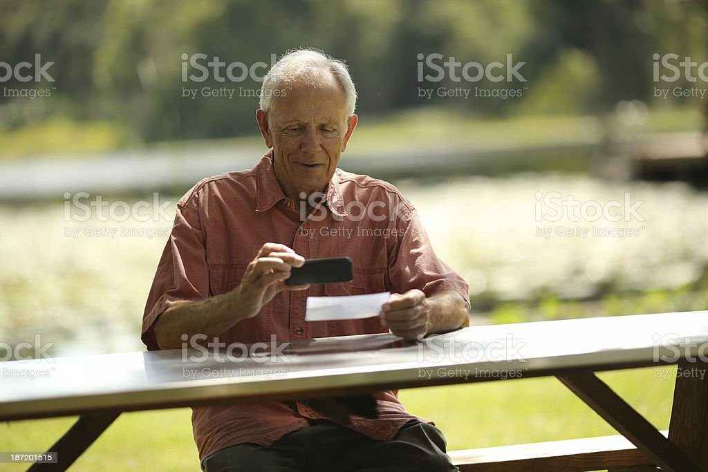 Happy Senior Man Depositing Check With Smart Phone royalty-free stock photo