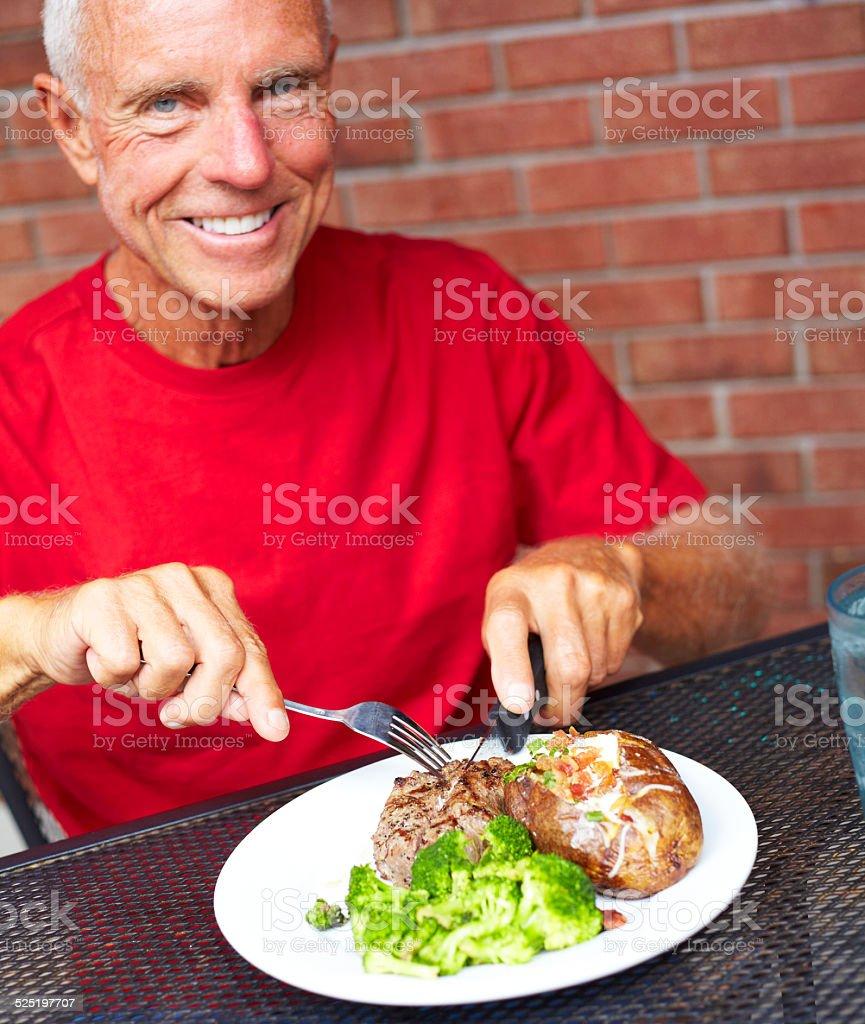Happy Senior Man Eating Strip Steak At Restaurant stock photo