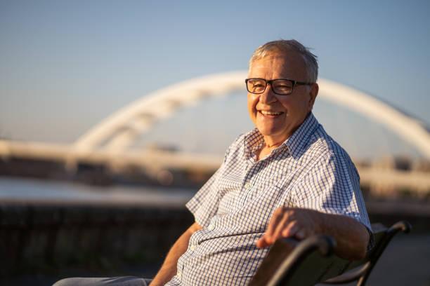 glücklicher senior mann genießt sonnenuntergang - einzelner senior stock-fotos und bilder