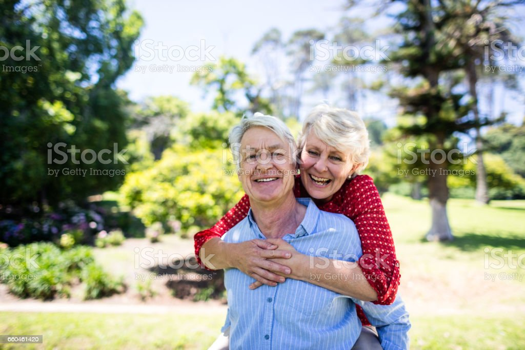 Happy senior man giving a piggy back to senior woman stock photo