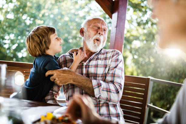 Happy senior man having fun with his small grandson during a meal on a balcony. Happy grandfather and grandson having fun during a meal on a terrace. grandson stock pictures, royalty-free photos & images