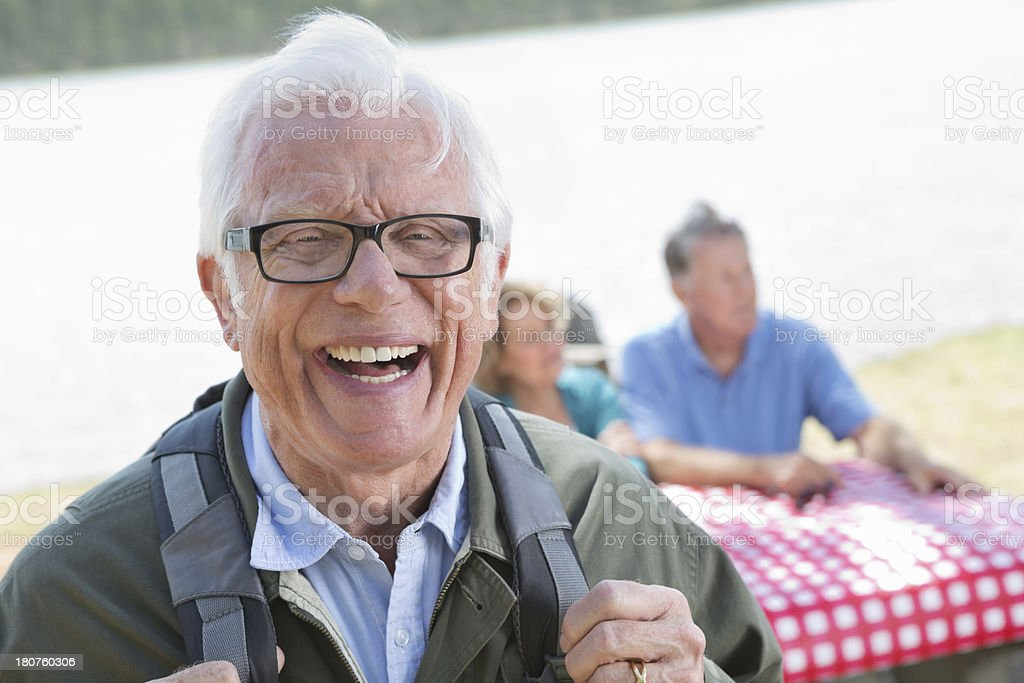 Happy senior man having picnic with friends near lake royalty-free stock photo