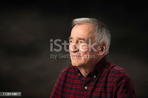 istock Happy Senior man in his late 70s studio portrait looking left with dark background 1128149817