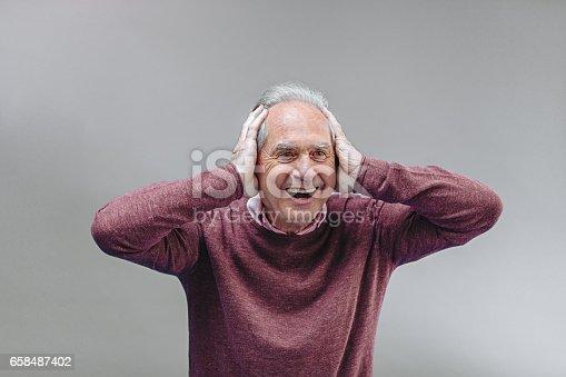 661896674istockphoto Happy senior man keeps shut ears 658487402