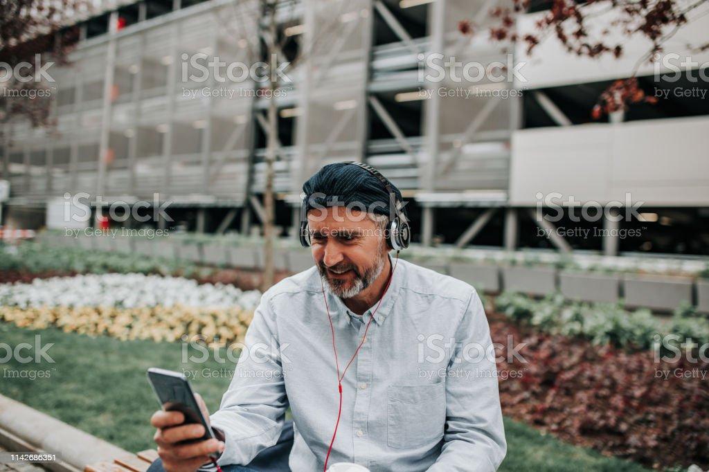 Happy senior man listening music playlist app and drinking coffee at...