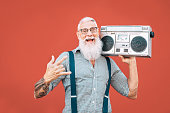 istock Happy senior man listening to music with boombox outdoor - Crazy hipster male having fun dancing with vintage stereo - Concept of elderly people lifestyle 1144429527