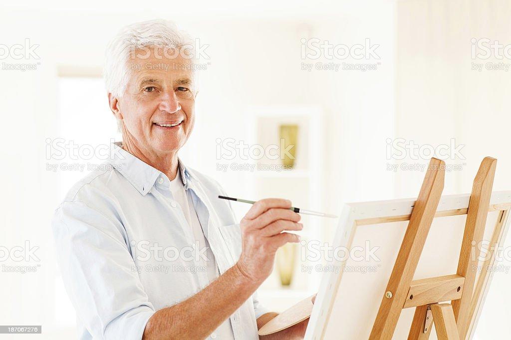 Happy Senior Man Painting On Canvas royalty-free stock photo