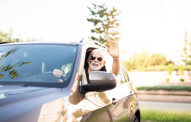 homme aîné heureux garant sa voiture et agitant à un ami. - homme faire coucou voiture photos et images de collection