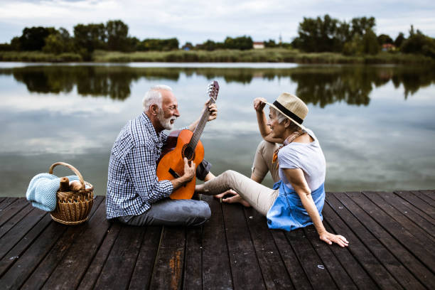 Happy senior man playing a guitar to his wife on a pier in nature. Happy mature man playing a guitar to his wife during romantic picnic on a pier. young at heart stock pictures, royalty-free photos & images