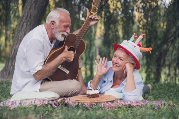 glücklicher senior mann spielt gitarre für seine frau, die geburtstag in der natur feiert - gitarren geburtstagstorten stock-fotos und bilder