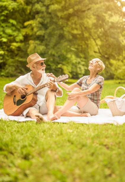 Happy senior man playing guitar to his wife while on a picnic in nature. stock photo