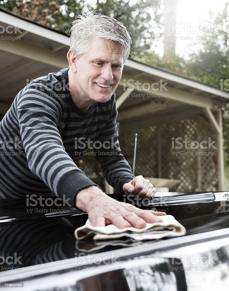 happy senior man polishing his car in front of a car port royalty-free stock photo